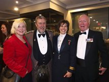 A photo of 4 smiling people in the Long Bar at the Royal Canadian Military Institute.
