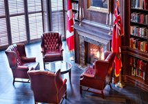 A photo of the Royal Canadian Military Institute library, with a fireplace and 4 comfortable chairs.